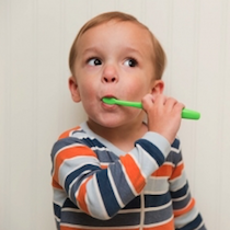 Young boy learning how to care for your teeth and the importance of brushing.